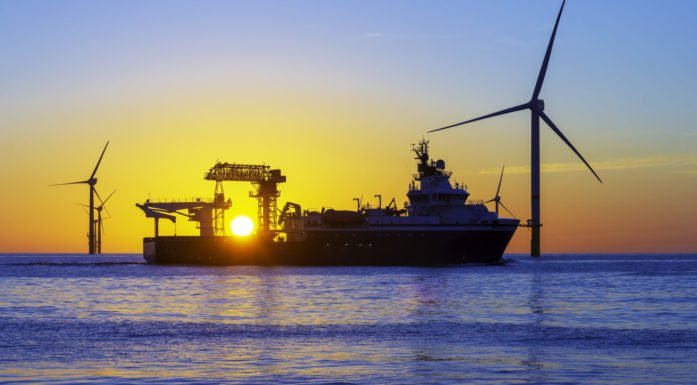 Ship and wind turbines at sea against sunset